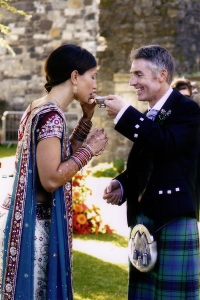 Groom in kilt with Indian bride in sari