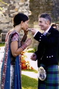 Groom in kilt with Indian bride in sari